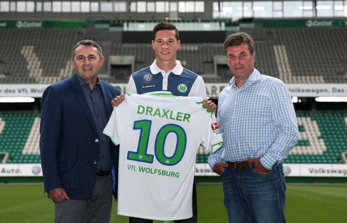 Julian Draxler posiert mit Wolfsburg's Sportdirektor Klaus Allofs (L) und Trainer Dieter Hecking (R) in der Volkswagen-Arena in Wolfsburg am 1.September 2015. AFP PHOTO / RONNY HARTMANN