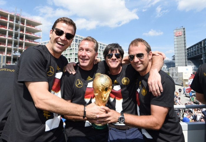 Teammanager Oliver Bierhoff, Torwarttrainer Andreas Koepke, Bundestrainer Joachim Loew und AssistenztrainerHansi Flick feiern am 15.Juli 2014 den WM-Titel in Berlin am Brandenburger Tor.  AFP PHOTO / POOL/ MARKUS GILLIAR