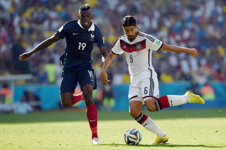 Frankreichs Paul Pogba (L) gegen Sami Khedirabeim WM 2014 Viertelfinale im Maracana Stadium von Rio de Janeiro am 4.Juli 2014. AFP PHOTO / PEDRO UGARTE