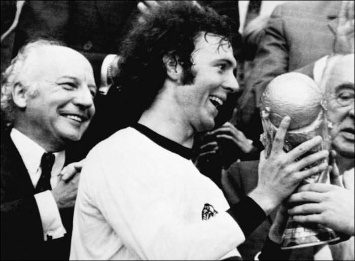Kapitän Franz Beckenbauer erhält WM-Pokal nach dem 2:1 Sieg gegen Holland am 07. Juli 1974 . Deutschlands damaliger Budnespräsident Walter Scheel (L) applaudiert. (Foto AFP)