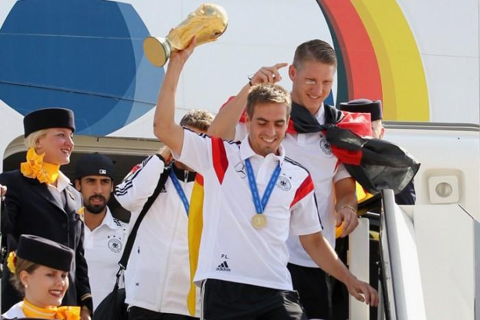 DFB Kapitän Philipp Lahm (C) hält den Welmeisterpokal 2014, Bastian Schweinsteiger ist ebenso wie Samy Khedira zu sehen beim Ausstieg in Berlin-Tegel. AFP PHOTO / POOL / KARINA HESSLAND / AFP / POOL / KARINA HESSLAND