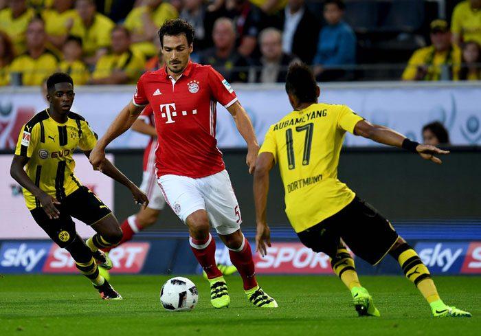 Bayern Münchens Abwehrspieler Mats Hummels (C) gegen Pierre-Emerick Aubameyang am 14.August 2016. / AFP PHOTO / PATRIK STOLLARZ