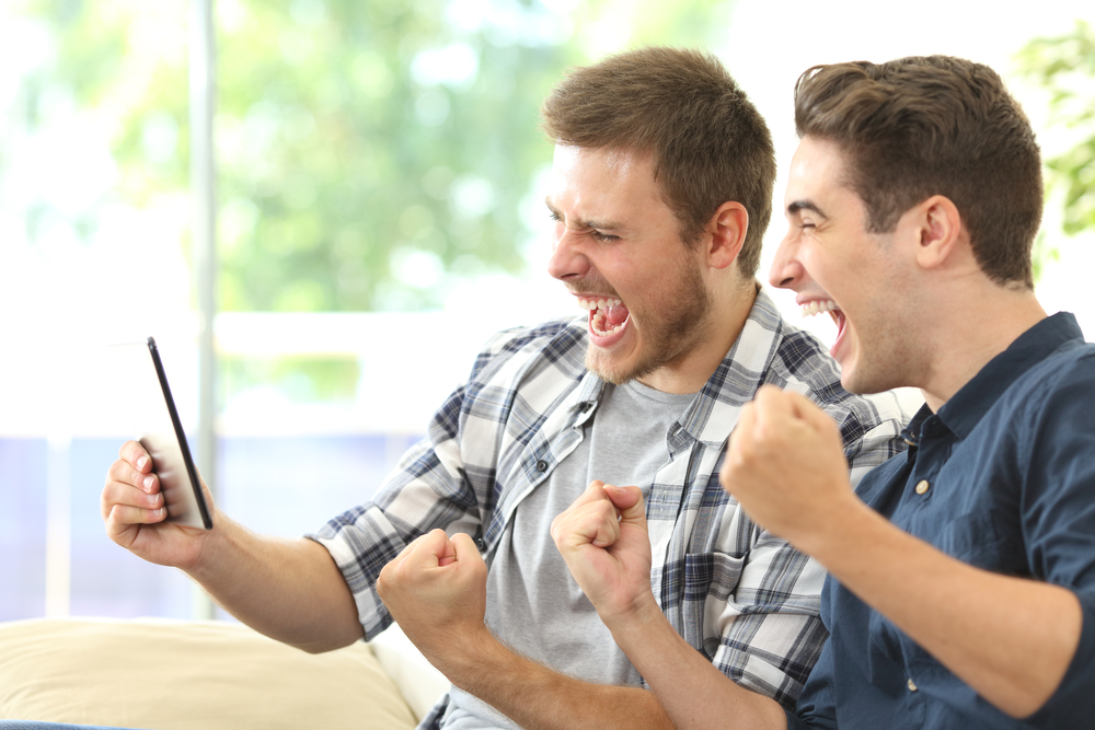 Zwei junge Männer freuen sich am Smartphone über Sportwettengewinn.
