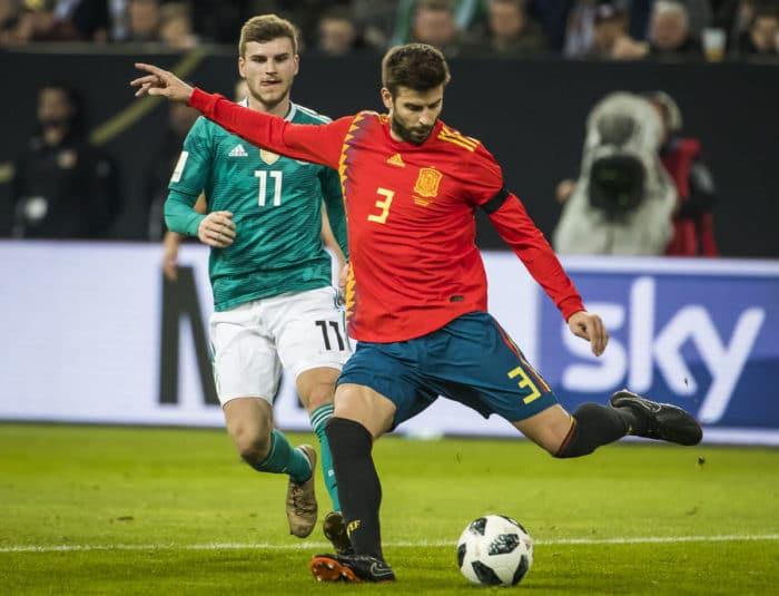 Timo Werner am 23.März 2018 im neuen grünen Away Trikot 2018 gegen Spanien - vorne Gerard Pique im neuen Spanien-Trikot 2018 (Foto AFP)
