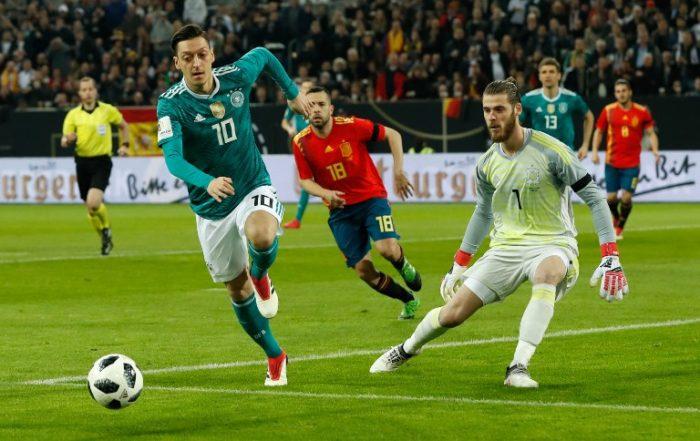 Mesut Özil im neuen Wm Trikot mit der Rückennummer 10, der spanische Torwart David de Gea (R) beobachtet am 23.März 2018 beim Testspiel gegen Spanien. / AFP PHOTO / Odd ANDERSEN