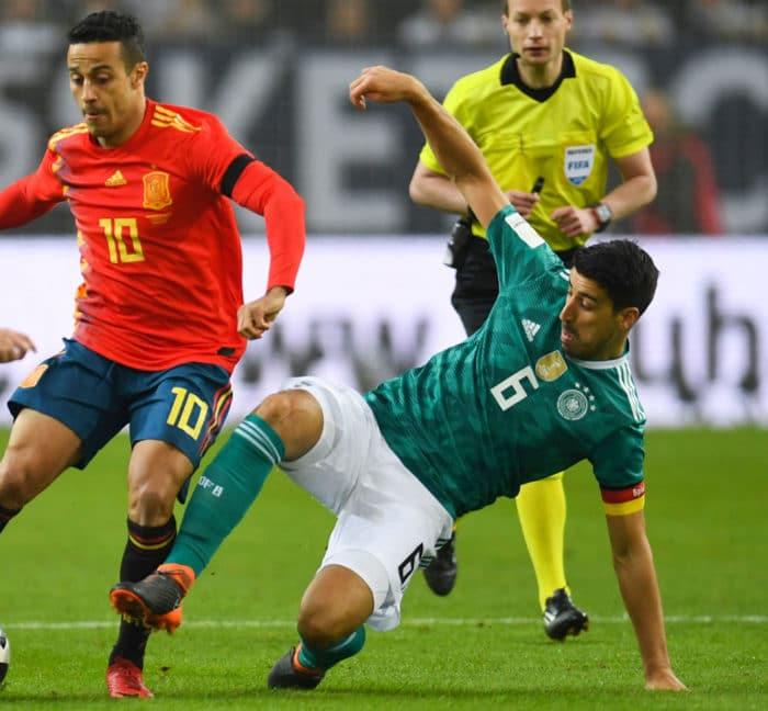 Spaniens Thiago Alcantara (C) und Sami Khedira (R) im Kampf um den Ball am 23.März 2018 / AFP PHOTO / Patrik STOLLARZ